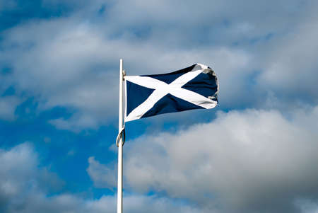 scottish flag in front of a sky full of clouds photo