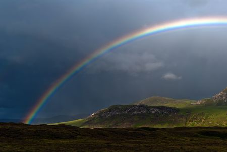 rainbow with dark sky over a meadow Stock Photo - 8063684