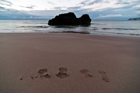 reproduced: two footprints on the beach at evening