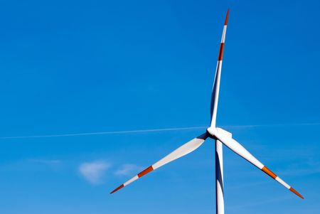 large wind turbine turns against a blue sky photo