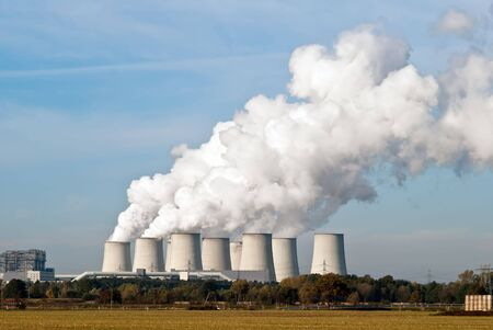 Cooling towers of a power plant with steam clouds and sky photo