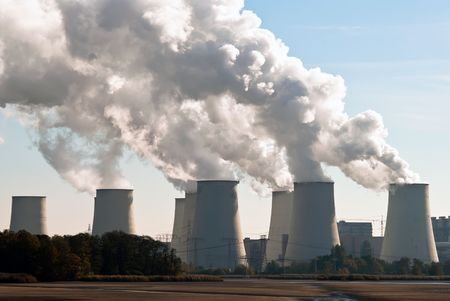 electricity prices: Cooling towers of a power plant with steam clouds and sky