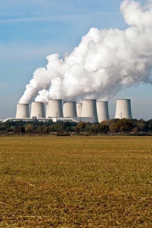 convection: Cooling towers of a power plant with steam clouds and sky