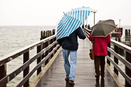 two people with an umbrella on the pier Stock Photo - 8153119