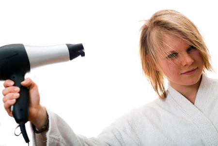 young blond woman with a hair dryer on a white background photo