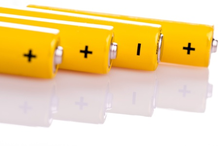 four yellow battery with positive and negative poles lying Stock Photo - 9052372