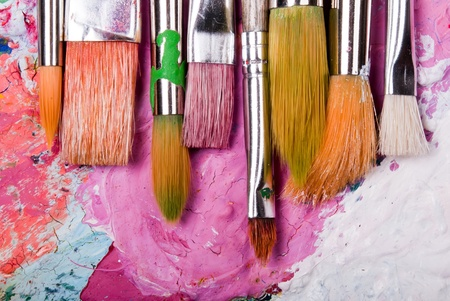 craft background: colorful color mixing palette with many brushes and text area below Stock Photo