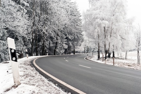 two-lane road with a curve through a winter landscape photo