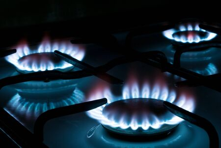 three flames burning on a gas stove in the kitchen