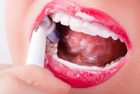 lower teeth: white teeth are brushed with an electric toothbrush Stock Photo