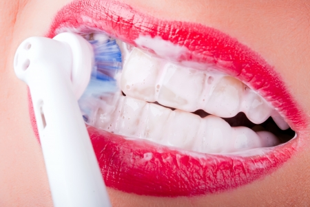 white teeth are brushed with an electric toothbrush Stock Photo