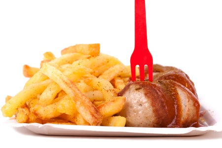 lunchbreak: a bowl with curried sausage and chips in front of white background Stock Photo