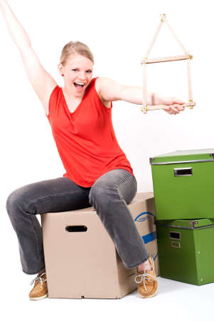 dynamically: a young woman with a folding rule as a house symbol sits on moving box