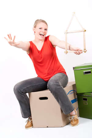 a young woman with a folding rule as a house symbol sits on moving box photo