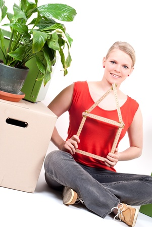 dynamically: young woman with a folding rule as a house symbol sits between move cardboards and a plant
