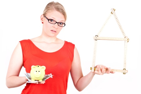 young woman with folding rule as a house symbol and piggy bank before white background photo