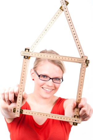 young woman with folding rule as a house symbol photo