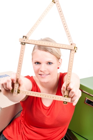 dynamically: young woman with a folding rule as a house symbol sits between move cardboards