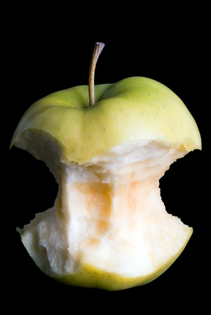 a apple core in front of black background photo