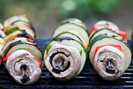 several vegetable spits lie on the grill