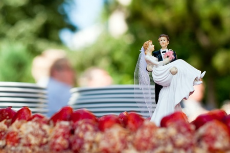 a figure of a bridal couple stands on a cake