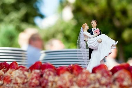 una figura de una pareja nupcial se levanta sobre un pastel