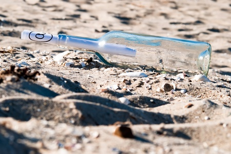 importantly: a message in a bottle with at-sign in the sand
