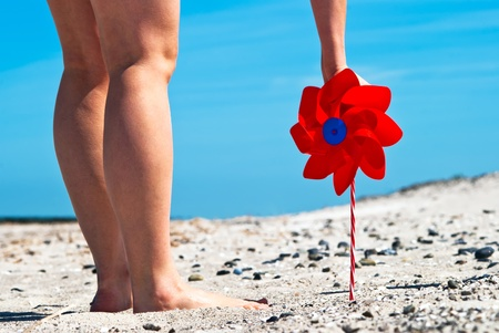 a red wind turbine on the sandy beach with two legs photo