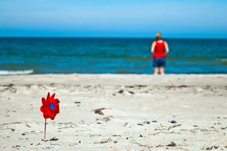 a red wind turbine on the sandy beach with sea in the background photo