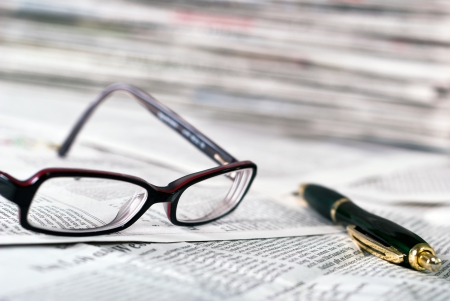 reading glasses and a ballpoint pen lie on a newspaper photo