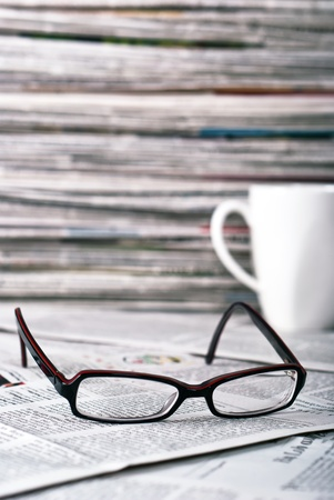 reading glasses and a coffee cup lie on a newspaper photo