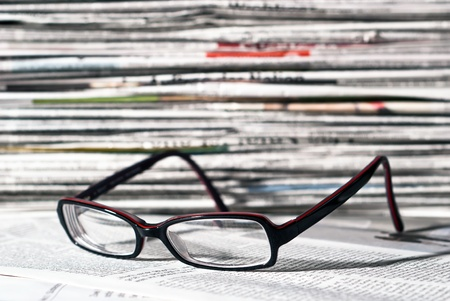 reading glasses lie before a big newspaper pile photo