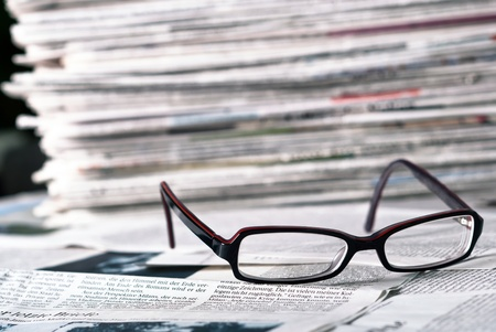 reading glasses lie before a big newspaper pile Stock Photo