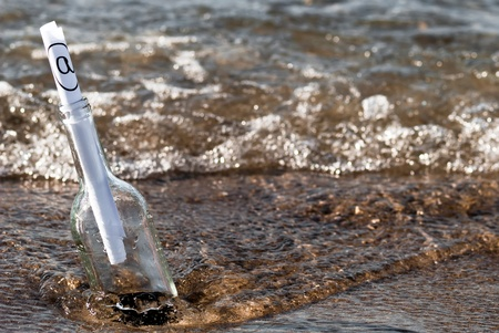a message in a bottle with an at-sign in the surge photo