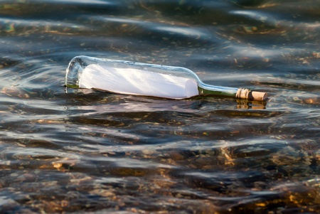 importantly: a message in a bottle swims in the water Stock Photo