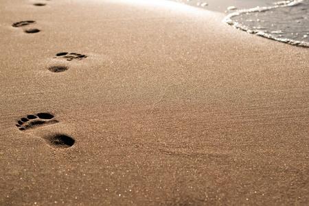 huellas de pies: pies de plomo puro en la arena a lo largo del agua Foto de archivo