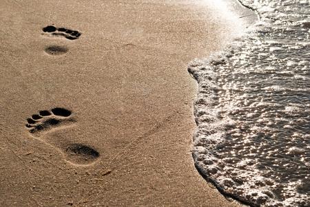 huellas de pies: puro de pie en el arena principal junto al agua Foto de archivo
