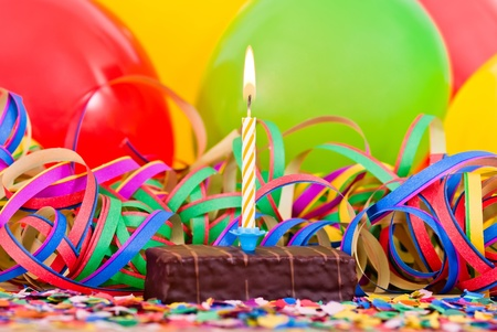 a burning candle on a small cake with streamers and balloons Stock Photo - 9979451