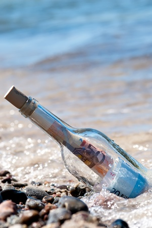 tax tips: a message in a bottle on the beach fullly with euronotes Stock Photo
