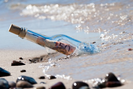 a message in a bottle on the beach fullly with euronotes photo