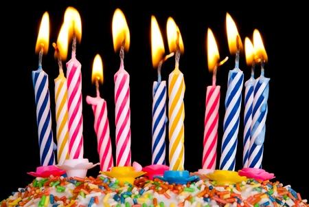 candeline compleanno: molte candele colorate bruciano prima di sfondo nero