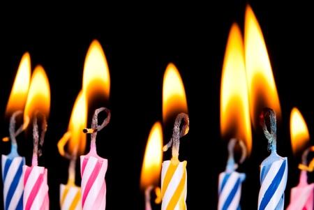 velas de cumpleaños: queman muchas velas de colores antes de fondo negro Foto de archivo