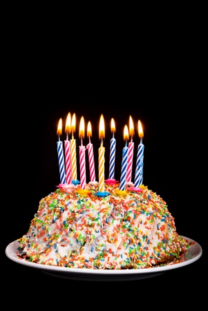 a cake with many coloured candles before black background photo