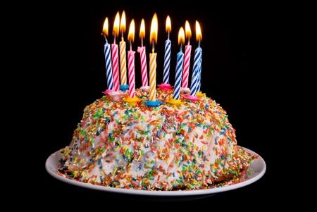 kerzen: ein Kuchen mit vielen farbigen Kerzen vor schwarzem Hintergrund