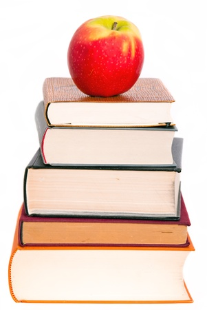 science lesson: a juicy apple lies on a book pile Stock Photo