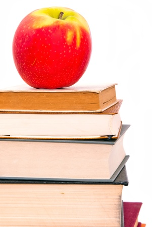 school things: a juicy apple lies on a book pile Stock Photo