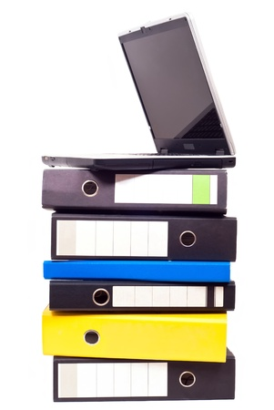 filing system: a laptop stands on files on white background Stock Photo