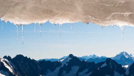 coldly: many icicles hang before snow covered mountain landscape Stock Photo