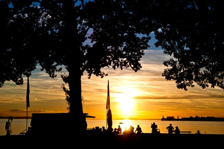 lake house: many people look at the sundown by the lake