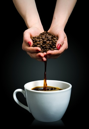 Coffee flows from a handful of beans into a cup photo
